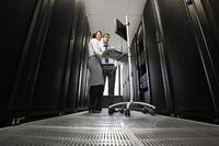 Two computer technicians working on servers